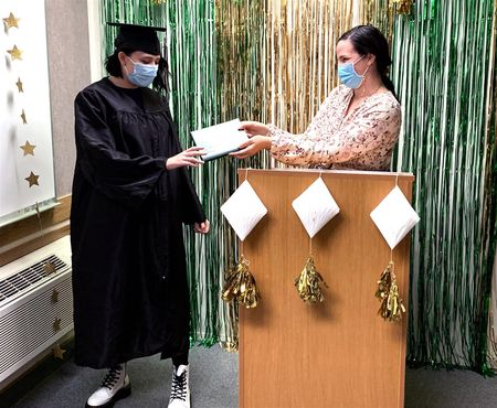 "Elizabeth ""Liz"" Vallaire, Math and Science teacher, presents Dakota Spencer with her diploma during a small commencement ceremony"